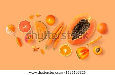 Creative layout made of carrot, papaya, orange, grapefruit, apricot, melon, tangerine , curcuma, and pepper on the orange background. Flat lay. Food concept. Macro  concept.