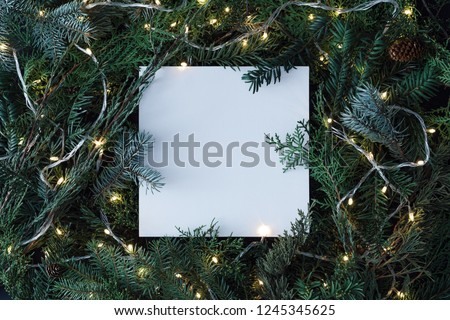 Creative layout made of Christmas tree branches with paper card note and christmas lights. Flat lay. Nature New Year concept. #1245345625