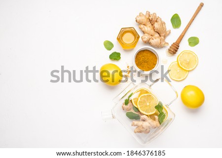 Creative layout made of clear glass teapot with ingredients. Hot seasonal tea against viruses. Ginger, turmeric, honey and lemon  ingredients. Immune system support with alternative medicine