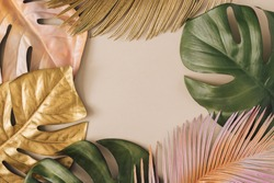 Creative layout made of colorful and golden tropical leaves and palms on beige background. Minimal summer exotic concept with copy space. Border arrangement background.