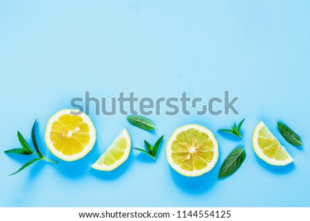 Creative layout made of fresh lemon slices and mint leaves. Ingredients for summer cocktail and lemonade on pastel blue background top view. Flat lay style #1144554125