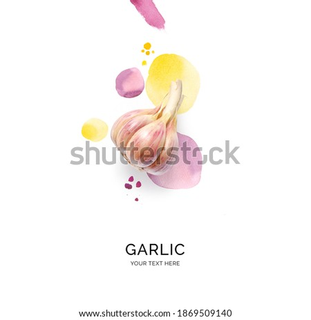 Creative layout made of garlic with watercolor spots on the white background. Flat lay. Food concept.