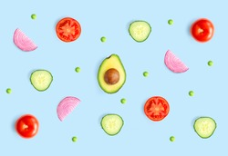 Creative layout made of green peas, avocado, tomato, onion and cucumber on the blue background.. Flat lay. Food concept.