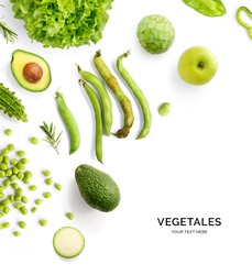 Creative layout made of green vegetables and fruits. Flat lay. Food concept. Avocado, broad bean, green peas, green apple, cherimoya, rosemary, zucchini and green lettuce on the white background.