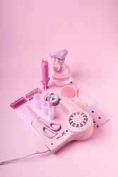 Creative layout made of hair dryer, scissors and accessories on pink background. Retro vintage 70's and 80's aesthetic with summer shadows. Flat lay.