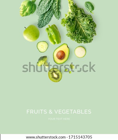 Creative layout made of kale, broccoli, green beans, zucchini, cucumber, apple, kiwi, lemongrass  on the green background. Flat lay. Food concept. Macro  concept.