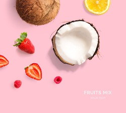 Creative layout made of lemon, strawberry and coconut. Flat lay. Food concept. Tropical fruits on the yellow background.