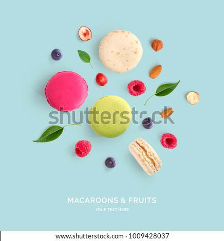 Creative layout made of macaroons, raspberry, blueberry and nuts . Flat lay. Food concept. Abstract background.
