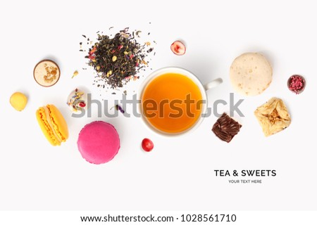 Creative layout made of tea, macaroons, praline on white background. Flat lay. Food concept.