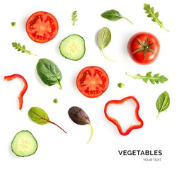 Creative layout made of tomato, cucumber and salad leaves on the white background. Flat lay. Food concept.