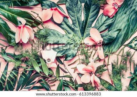 Creative layout made of tropical flowers and palm leaves on pastel pink background, top view,  flat lay #613396883