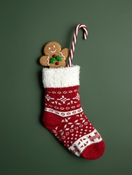 Creative layout made with Christmas socks, gingerbread man and candy cane on green background. Minimal New Year season concept. Top view, flat lay.