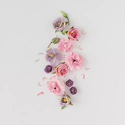 Creative layout made with pink and violet flowers on bright background. Flat lay. Spring minimal concept.