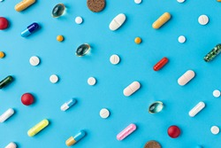 Creative layout of pills and capsules on blue background with summer sun and sharp shadow. Covid-19 or Coronavirus minimal art concept.