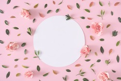 Creative layout pattern with green and red leaves and pink flowers with white copy space. Nature flat lay. Minimal spring concept.