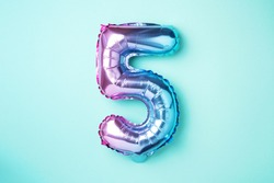 Creative layout. Rainbow foil balloon number and digit five 5. Birthday greeting card. Anniversary concept. Top view. Copy space. Stylish colored numeral over blue background. Numerical digit