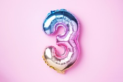 Creative layout. Rainbow foil balloon number and digit three 3. Birthday greeting card. Anniversary concept. Top view. Copy space. Stylish colored numeral over pink background. Numerical digit