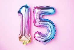Creative layout. Rainbow foil balloon number, digit fifteen. Birthday greeting card with inscription 15. Anniversary concept. Top view. Stylish colored numeral on pink background. Numerical digit.