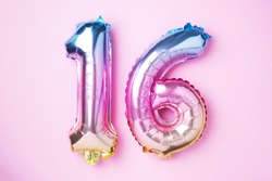 Creative layout. Rainbow foil balloon number, digit sixteen. Birthday greeting card with inscription 16. Anniversary concept. Top view. Stylish colored numeral on pink background. Numerical digit.