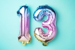 Creative layout. Rainbow foil balloon number, digit thirteen. Birthday greeting card with inscription 13. Anniversary concept. Top view. Stylish colored numeral on blue background. Numerical digit.