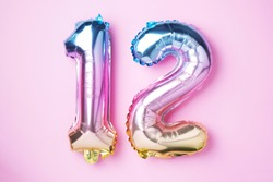Creative layout. Rainbow foil balloon number, digit twelve. Birthday greeting card with inscription 12. Anniversary concept. Top view. Stylish colored numeral on pink background. Numerical digit.