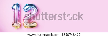 Creative layout. Rainbow foil balloon number, digit twelve. Birthday greeting card with inscription 12. Anniversary concept. Top view. Stylish colored numeral on pink background. Numerical digit. Stock photo ©