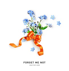 Creative layout with blue forget me not spring flowers and orange ribbon bow isolated on white background. Floral composition and arrangement. Springtime and mothers day concept, flat lay