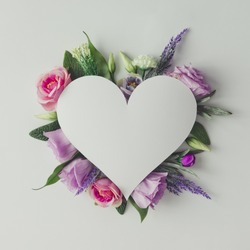 Creative layout with colorful flowers, leaves and heart shape. Anniversary concept.Flat lay.