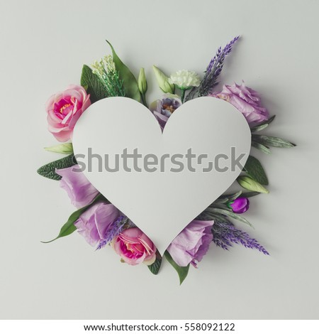 Creative layout with colorful flowers, leaves and heart shape. Anniversary concept.Flat lay. #558092122