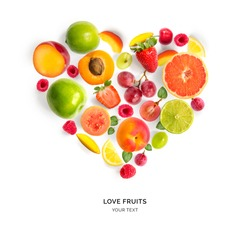 Creative layout with heart shape by various fruits. Heart of grape, apricot, raspberry, strawberry, lemon, apple, plum. Flat lay.