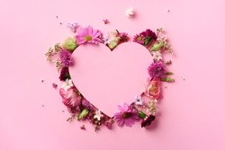 Creative layout with pink flowers, paper heart over punchy pastel background. Top view, flat lay. Spring, summer or garden concept. Present for Woman day.