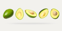 Creative layout with ripe flying avocado halves on light background. Healthy food, diet, tropical exotic fruit, trendy food product. Minimalistic summer food concept. Organic avocado. Pop art design