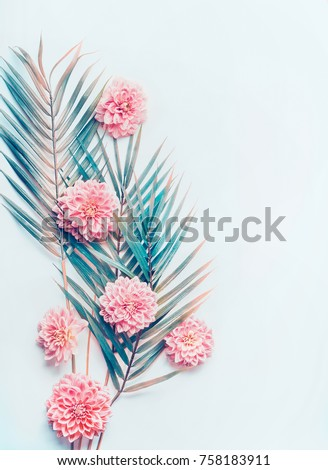 Creative layout with tropical palm leaves and pastel pink flowers on  turquoise blue desktop background, top view, place for text, vertical #758183911