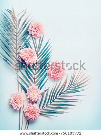 Creative layout with tropical palm leaves and pastel pink flowers on  turquoise blue desktop background, top view, place for text, vertical #758183992