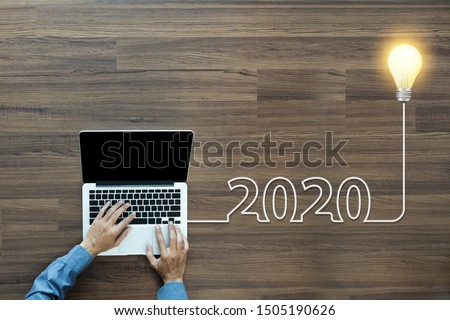 Creative light bulb idea 2020 new year, With businessman working on laptop computer PC, Top view from above