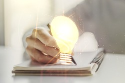 Creative light bulb illustration with hand writing in notepad on background, future technology concept. Multiexposure