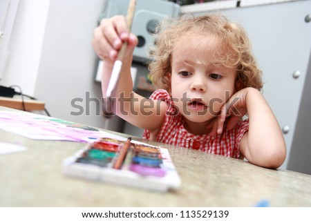 Creative little girl draws in classroom/Budding artist. - stock photo