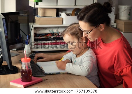 Creative little girl writing on the paper while sitting on mother's lap.