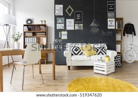 Creative living room with chalkboard wall, wooden desk and vintage furniture #519347620
