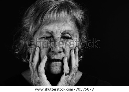 Creative low key black and white to emphasize dramatic facial expression of senior woman.