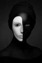 Creative make-up and beauty theme: portrait of beautiful young girls model with black and white body art on face and black clothes with a lens in the eye on a dark background in the studio