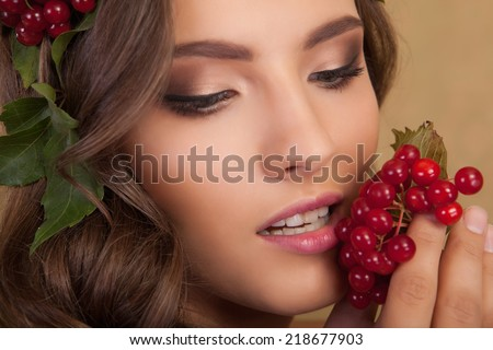 Creative makeup. Young beautiful girl with make-up with a berry and a leaf on yellow background.