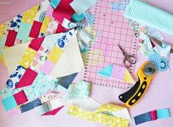 Creative mess: fabric scraps, scissors, rotary cutter, seam ripper, quilting ruler and cutting mat