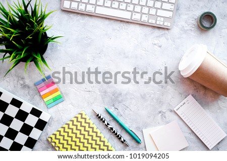 Creative mess on student's desk. Keyboard, stationery, coffee cup, plant on grey background top view copy space