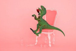 creative minimal poster with drunk dinosaur holding glass of wine on a pink background and sitting on a pink chair
