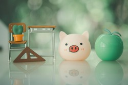 Creative minimalist photo of student desk, green apple and pig doll. The concept of back to school