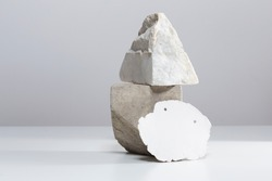 Creative minimalist sculpture arrangement on table, random stones and irregular white clay plate composition