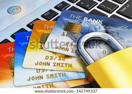 Creative mobile banking, commerce and security payment financial business concept: macro view of group of color credit cards and golden padlock on laptop computer PC notebook keyboard