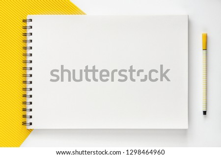 Creative mockup desk. View from above. Yellow fluted paper. Empty open sketchbook with space for text. Geometric minimal composition