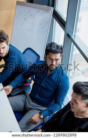 Creative multiethnic business team in the modern conference room discuss work results siiting at the table against big window background. Focus on handsome Indian guy in dark formal shirt.